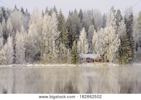 Little cottage by the river in the freeze