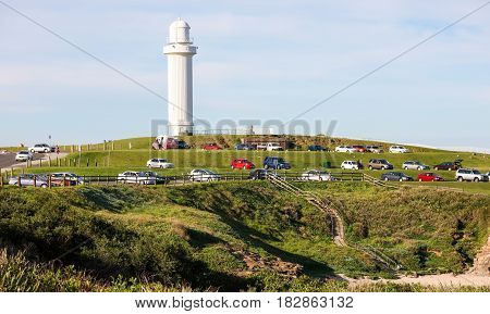 Wollongong Head Flagstaff Lighthouse, with vehicles parked and looking south over Pacific Ocean