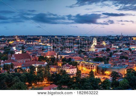 Vilnius, Lithuania. Historic Center Cityscape At Blue Hour After Sunset. Old Town Under Evening Dusk Sky. Travel Panorama In Night Illuminations. UNESCO World Heritage Site. Sts Johns' Church