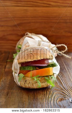 Vegetarian burger wrapped in paper and tied with twine, vertical