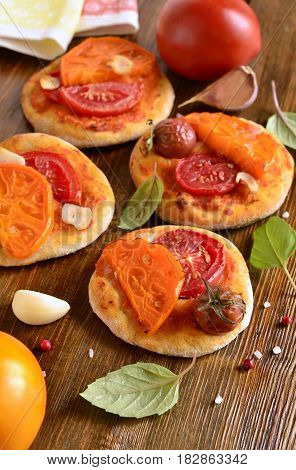 Small homemade pizza with tomatoes and basil, vertical