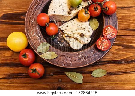homemade cheesetomatos with herb spice in brown pottery.wooden background