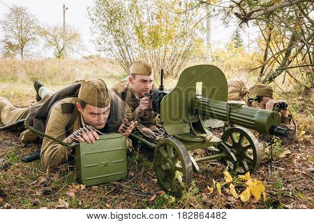 Dyatlovichi, Belarus - October 1, 2016: Reenactors Dressed As Russian Soviet Red Army Soldiers Of World War II Hidden Sitting With Maxim's Machine Gun Weapon In An Ambush In Autumn Forest