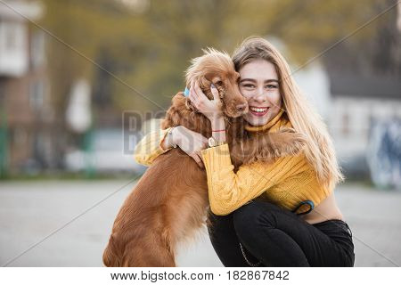Portrait. Beautiful sexy girl, blonde, young woman, similar to Jennifer Aniston siting with a dog cocker spaniel, hugs, touches, cares. Against the background of city houses.