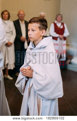 Vilnius, Lithuania - July 6, 2016: Boy taking part in procession in Cathedral Basilica of Saints Stanislaus and Vladislaus during celebration of Statehood Day. Holiday in commemorate coronation in 1253 of Mindaugas King.