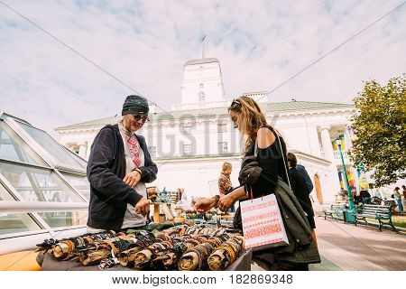 Minsk, Belarus - September 3, 2016: Woman Buying Souvenirs  On Street Market In Freedom Square Near Town Hall. Trading trays With Sale Of Gifts, Sweets And Souvenirs Made From Wood, Straw And Clay