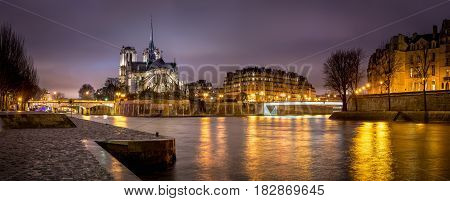 Evening panoramic view of Notre Dame de Paris Cathedral on Ile de La Cite with city lights reflecting on the Seine River. Visible are the Archbishop's Bridge Pont Saint Louis (also known as Passerelle Saint Louis) and the tip of Ile Saint Louis. 4th Arron