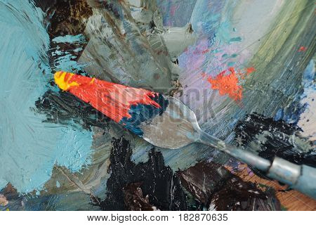 Palette knife with oil painting colors on pallette background