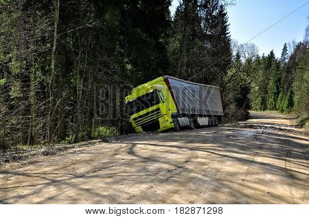 Yellow truck crashed to the forest road.