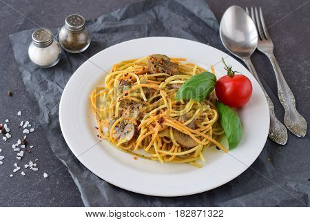 Pasta with mushrooms and pesto sauce in a white plate on abstract bckground. Italian lifestyle. Healthy eating concept