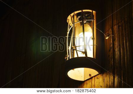 electric lamp hanging on bamboo wall in the night