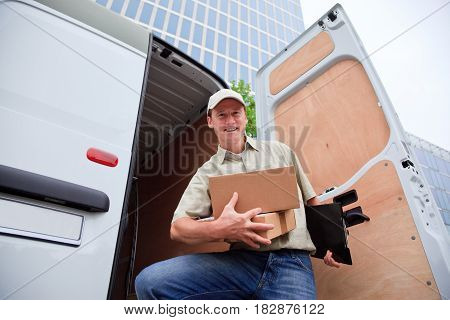 a smiling delivery person is standing next to his white van parked in front of modern buildings.