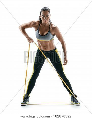 Athletic young girl performs exercises using a resistance band and looking at the camera. Photo of young girl isolated on white background. Strength and motivation