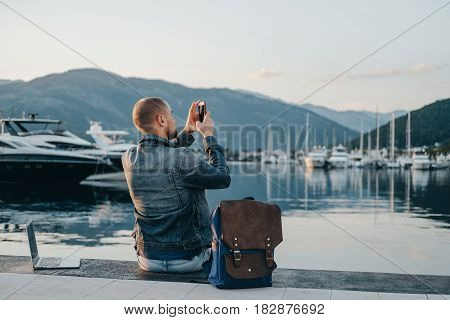 Freelancer Taking Photo And Working On Laptop On The Shore Near The Yacht Boat At Rest