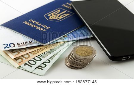 Tourism travel and objects concept - Euro money smartphone and Ukraine passport on table