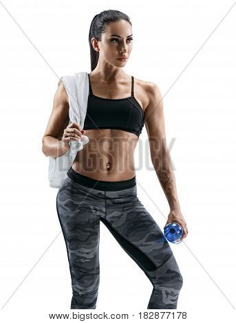 Resting time. Beautiful athletic woman with towel on shoulders holding bottle of water. Health concept.