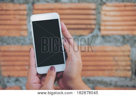 Mockup image of hand holding white mobile phone with blank black screen and brick wall background