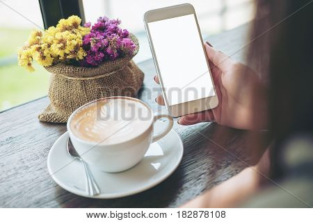 Mockup image of hands holding white mobile phone with blank white screen with hot coffee cup and flower vase in cafe