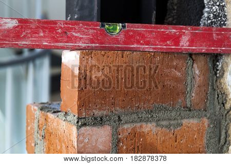 Close up of bricklaying industrial installing bricks on construction site wall with working tools mortar level