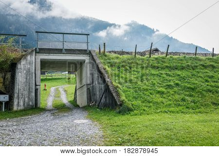 Small tunnel under the railroad with green grass in autumn Switzerland