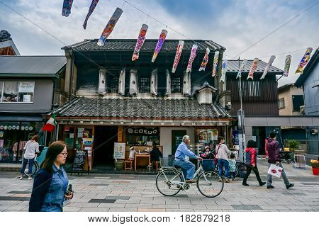 JAPAN - April 6 2015: People walk and cycling in old city of Kawagoe with fish carp windsocks decoration in The Boy's Festival. Kawagoe Japan