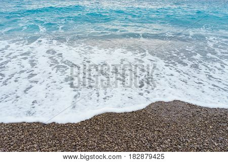 selective focus Soft gentle waves with foam in blue ocean italy coast summer vacation as background