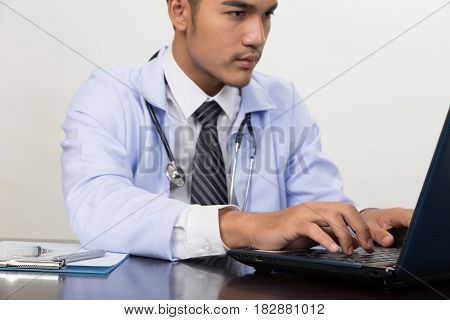 Male Doctor Typing On Laptop Computer