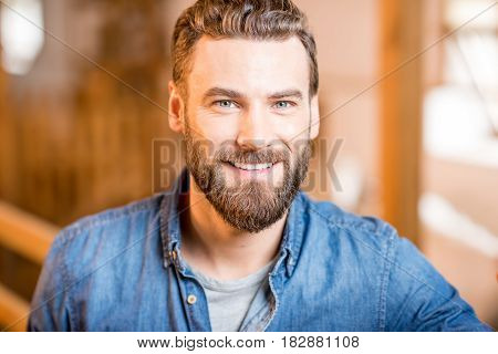 Close-up portrait of a handsome businessman or farmer indoors in the barn