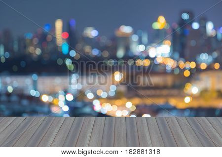 Blurred bokeh light city downtown night view abstract background opening wooden floor