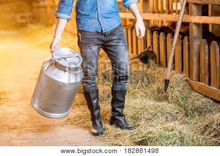 Close-up view on the legs of farmer working with hay at the animal barn