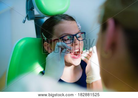 Close up of girl having his teeth examined by a dentist - dental caries prevention