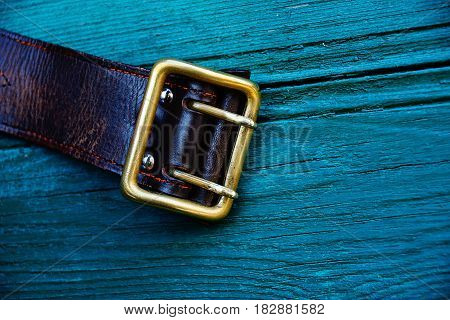 Brown leather belt with a copper buckle on green boards