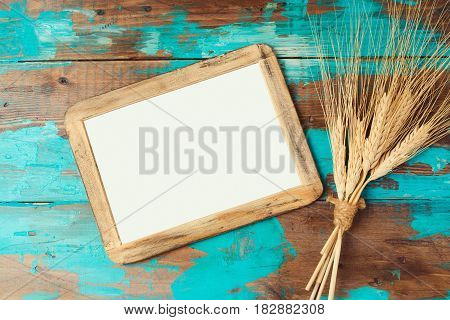 Poster frame and wheat crop on wooden background. Jewish holiday Shavuot concept. View from above