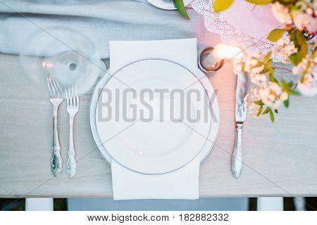 Table setting with dishes, glass, cutlery, candle and beautiful floristic. Decor for wedding