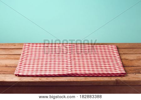 Empty wooden deck table with checked tablecloth over mint background for product montage display