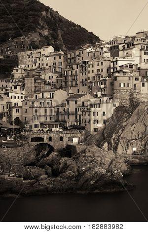 Manarola overlook Mediterranean Sea with buildings over cliff in Cinque Terre, Italy. Black and white.