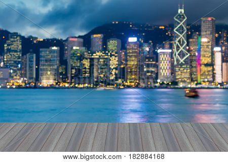 Opening wooden floor Blurred bokeh light office building seafront Hong Kong city abstract background