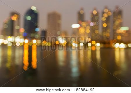 Office building blurred bokeh light with water reflection abstract background