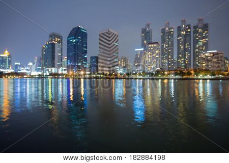 Night blurred bokeh light office building water front abstract background