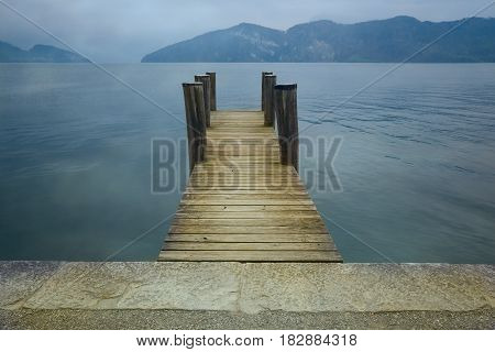 Wooden pier on lake. Vacation tourism and adventure concept. Retro filter effect