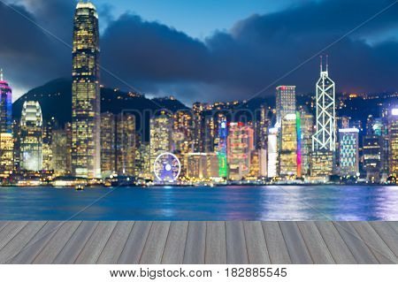 Opening wooden floor Hong Kong city blurred bokeh light seafront with twilight sky abstract background
