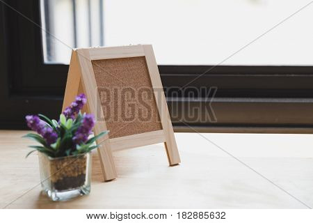 Corkboard, Artificial Flower In Small Glass Pot On A Wooden Table.