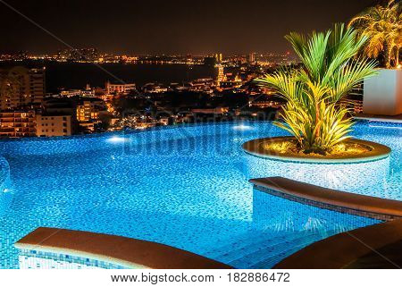 A beautifully illuminated swimming pool on top of a tall building with the city in the background