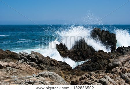 A strong wave crashing on rocky shore