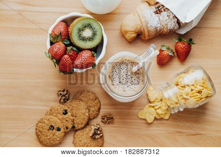 Sweet Breakfast With Coffee, Milk, Corn Flakes, Cookies, Croissant, Strawberry, Kiwi On A Wooden Tab