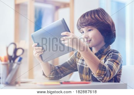 I didn't now that. Pre-adolescent boy with brown hair wearing a checked shirt reading on a dad's digital tablet while sitting at a writing desk