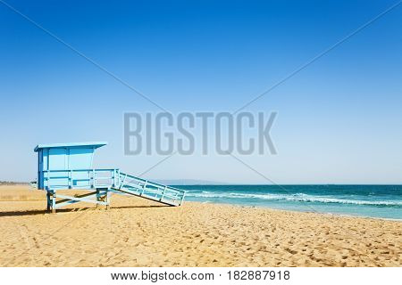 Side view picture of blue lifeguard tower on a sandy beach of Santa Monica, California, USA