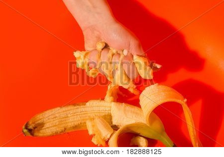 Vitamin and healthy eating. Female hand squeezing juice or squash from banana ripe mellow fruit and peeled yellow skin on bright orange background