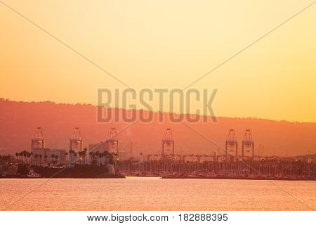 The Port of Long Beach with working crane bridges, ships and yachts at dusk, view from the sea