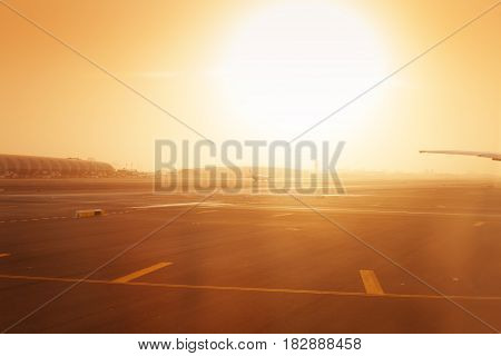 Airplane taxiing on an Dubai International Airport runway in haze